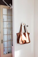 Brown leather bag hanging on peg next to lattice door