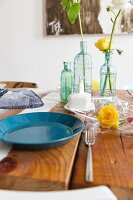 Blue plate and flowers in glass vases on wooden table
