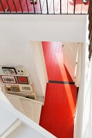 View down onto red-painted wooden floor in open-plan stairwell
