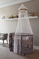 Oval cot with canopy, storage baskets on white shelf on pale grey wall