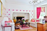 Living room with pink accents, white sofa set and black coffee table in front of open fireplace