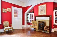 Masonry arch with integrated fireplace and fitted display cases and gilt, Rococo chairs in room with red walls