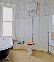 Toilet with vintage cistern, free-standing bathtub and toile-de-jouy wallpaper in bathroom with white wall tiles