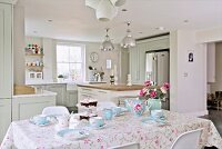 Breakfast table set with pale blue crockery in front of open-plan, country-house kitchen