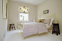Double bed with white, antique metal frame in bedroom painted pale grey with patterned roller blind on lattice window