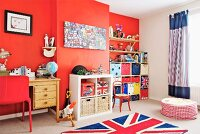 Child's bedroom with red wall, Union Flag rug, wooden desk and colourful storage boxes in fitted shelving in niche