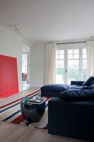 Blue sofa and drum-shaped side table on striped rug opposite red artwork leaning against wall