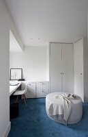 Pale ottoman on blue carpet, white fitted wardrobe and workspace with classic chair