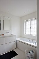 Washstand with white base unit next to bathtub below window in contemporary bathroom