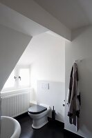 Toilet in white, attic bathroom with black wooden floor
