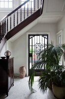 Staircase with turned wooden balusters in foyer with potted palms in front of glass front door