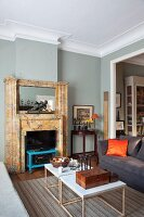 Delicate coffee table and open fireplace in elegant living room with grey-painted walls and stucco moulding