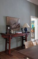 Table clock and table lamp on antique, carved, Oriental-style console table against grey-painted wall