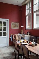 Traditional kitchen with antique chairs at dining table and walls painted Bordeaux red
