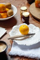 Fresh lemon and knife on white, leaf-shaped plate