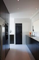 Black designer kitchen with pale worksurface and floor-to-ceiling cupboards with fitted appliances; notes written in chalk on door painted with chalkboard paint