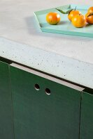 Close-up of DIY kitchen counter with concrete worksurface and hole pulls in dark green doors; tangerines on tray
