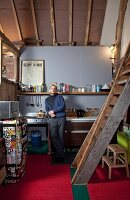 Young man in DIY loft-apartment kitchen with rustic ladder leading to gallery and retro fridge covered in colourful stickers on red carpet