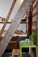 Pale green metal table against brick wall below wooden ladder; kitchen counter with pale grey back wall in background