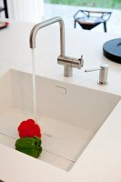 White sink in designer Corian kitchen worksurface; water running onto bell peppers