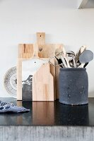 Kitchen utensils in clay container and wooden chopping boards
