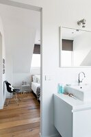 Washstand in bathroom and view of bedroom through open doorway