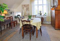 Simple, traditional dining room with sloping ceiling, antique wooden chairs and dresser