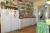 Kitchen counter with white base units, crockery on wall-mounted bracket shelves and fridge-freezer combination in simple country-house kitchen