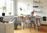 Boy's bedroom with desk, wall-mounted shelves, wooden chairs and vintage wooden crate