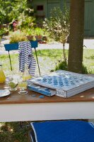 An old board game and a cold drink on a table in a garden with a blue cushion and a maritime t-shirt on garden chairs