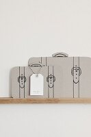 Suitcase silhouettes in grey card with painted-on straps and card name tag