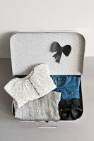 Folded girl's clothing and bow silhouette cut out of black paper in open, child's suitcase