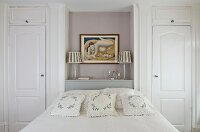 Bed with floral, lace scatter cushions below painting of woman in niche flanked by fitted wardrobes with panelled doors