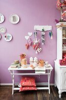 Ornaments on white console table with cushions on base frame below decorations hanging from hooks and painted plates on lilac wall