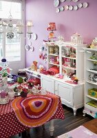 Shop with lilac-painted walls and ornaments on table in front of shabby-chic cabinet
