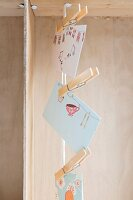 Cards with colourful motifs hung from vertical cord using clothes pegs