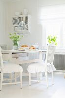 White-painted, wooden furniture in shabby-chic dining area in kitchen-dining room