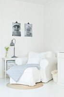 White armchair in corner, grey lamp on side table and black and white photos on wall