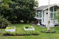 Vegetable beds with and without wooden surrounds in lawn next to Swedish summerhouse
