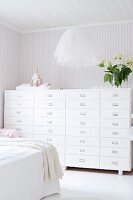 Pendant lamp with tulle lampshade and chest of drawers against pale, striped wallpaper in bedroom