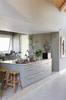 Pale grey island counter with drawers in open-plan designer kitchen