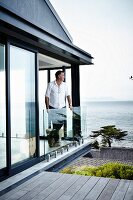 Contemporary house; man leaning on glass balustrade in open balcony doors