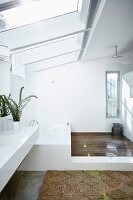 White designer bathroom; long washstand with bathtub at far end in floor-level shower area below large skylights
