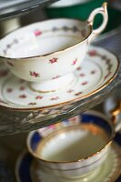 Antique gold-rimmed teacups with floral patterns and matching saucers