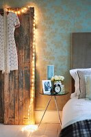 Dress hanging on removed vintage doors leaning against wall and decorated with fairy lights next to modern side table and partially visible bed