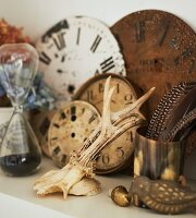 Antlers, brass pot of feathers and vintage clock faces on white shelf