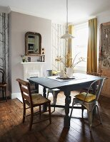 Wood and metal chairs around wooden table with turned legs painted pale grey in traditional dining room