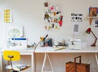 Improvised desk on trestles below mood board with office utensils on wall