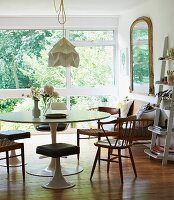 Tulip table, matching stools and wooden chairs in contemporary interior with view of garden
