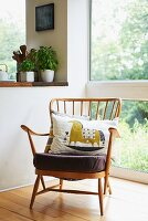 Fifties armchair with cushions next to glass wall and potted herbs on kitchen surface